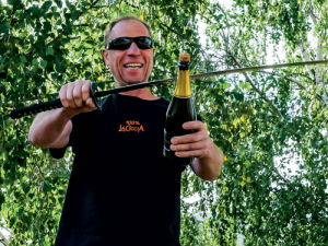 Rudi Brauer uses the traditional French Sabrage technique to open a bottle of Sparkling wine.