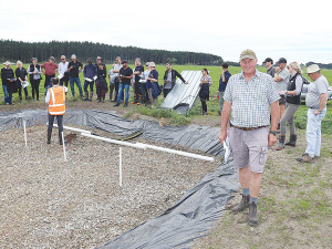 Hew Dalrymple pictured beside the woodchip bioreactor, which has been installed at the end of one of the drains on his farm.