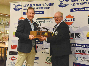 Ian Woolly (right) receives his trophy for winning the silver class at this year's NZ Ploughing Champs from Nathan Winter of Farmlands Fuel.