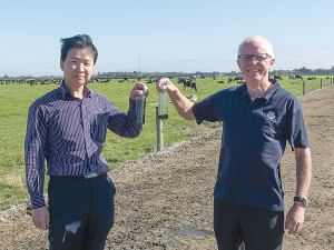 Lincoln University Professors Hong Di (left) and Keith Cameron show bottles of effluent, one raw and one cleared by the coagulant used in ClearTech system.