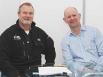 Brendon Cane (Precision Farming), left, and Wayne McNee (LIC) signing the agreement at National Fieldays.
